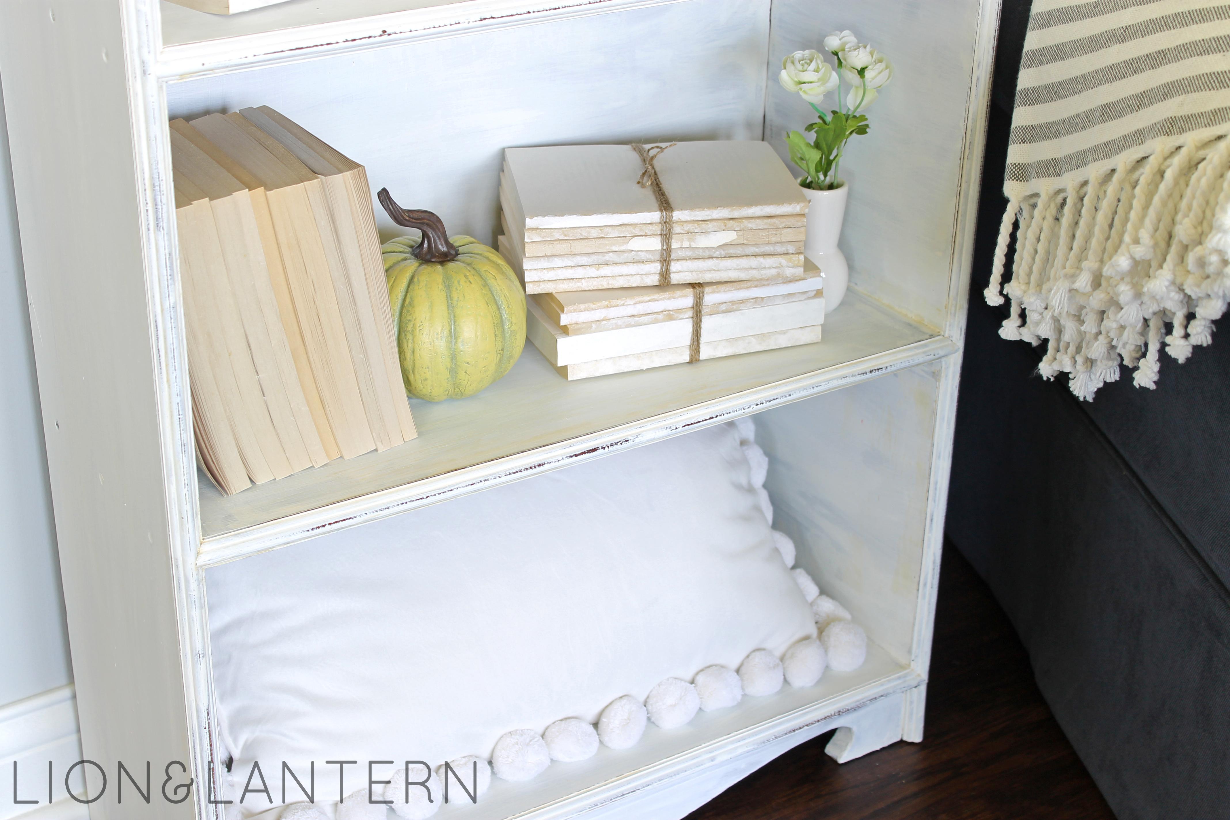 Cozy Autumn Bookcase Decor at LionAndLantern.com. Book bundle, neutral pumpkin, pom pom pillow.