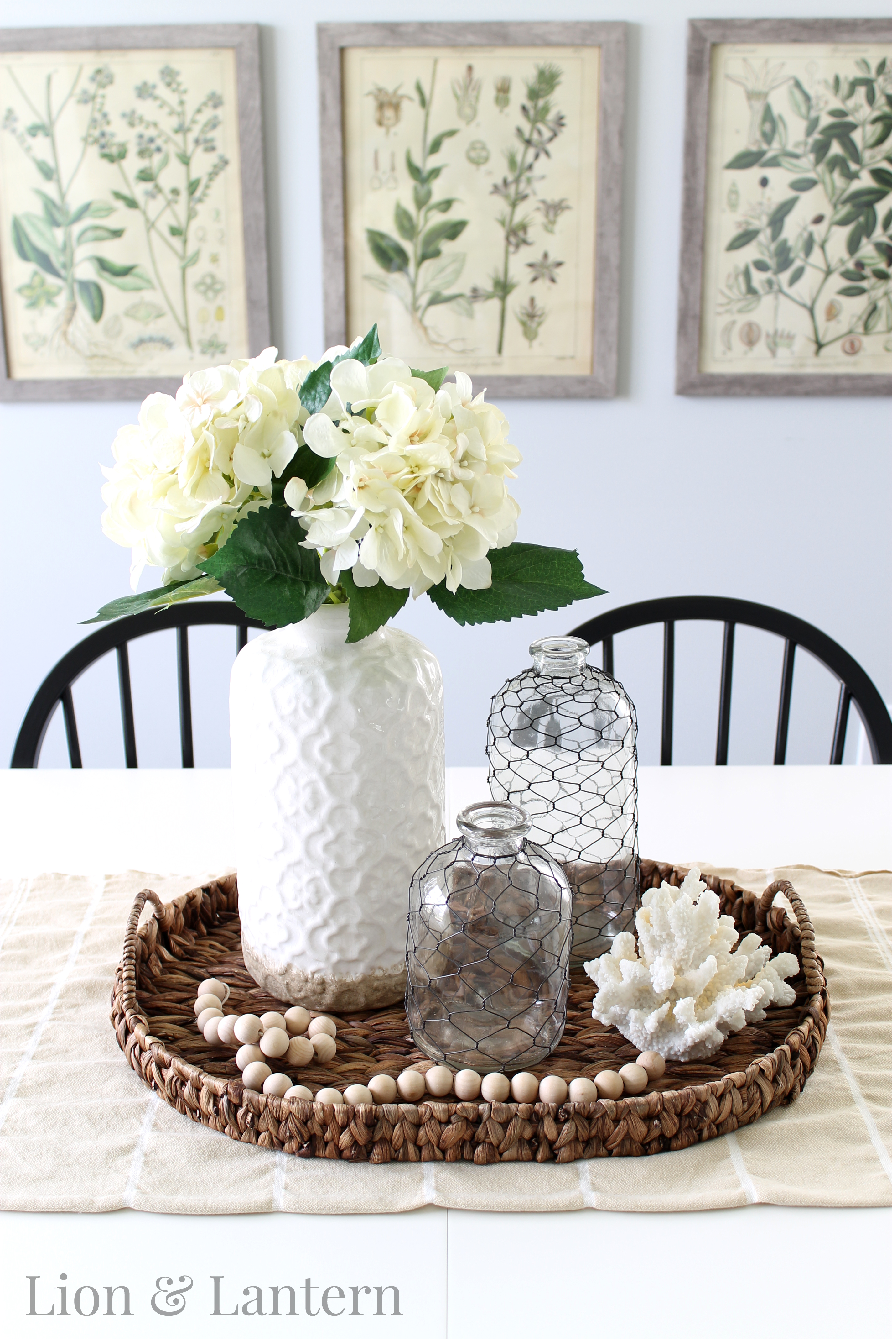 Coastal Farmhouse Dining Room at LionAndLantern.com. Botany prints, botanical prints, hydrangeas, coral, wood bead garland.