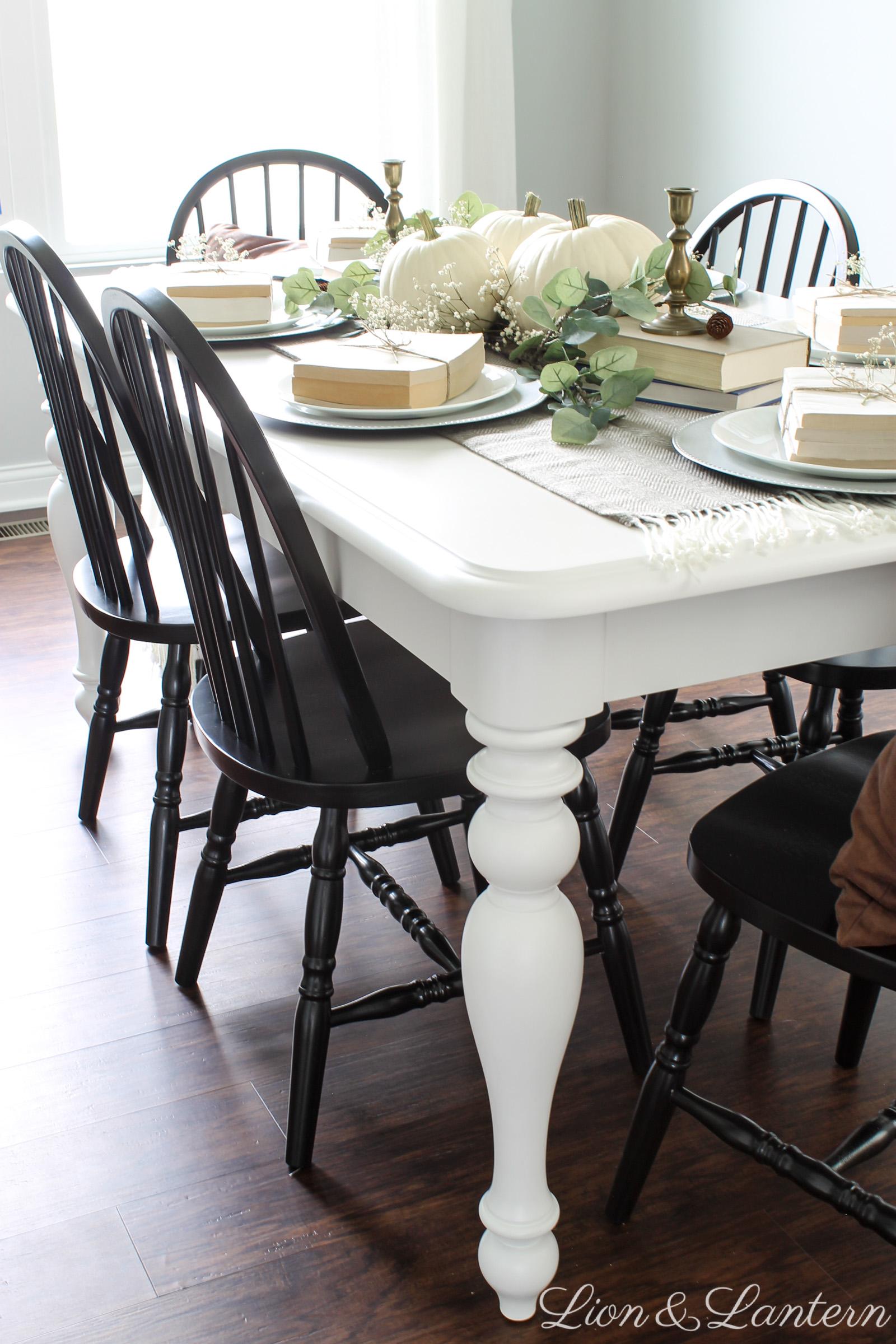 Thanksgiving Tablescape at LionAndLantern.com. Farmhouse Thanksgiving, Thanksgiving table decor, holiday decor, neutral, budget, eucalyptus, white pumpkins, book bundles, black chairs, white table.