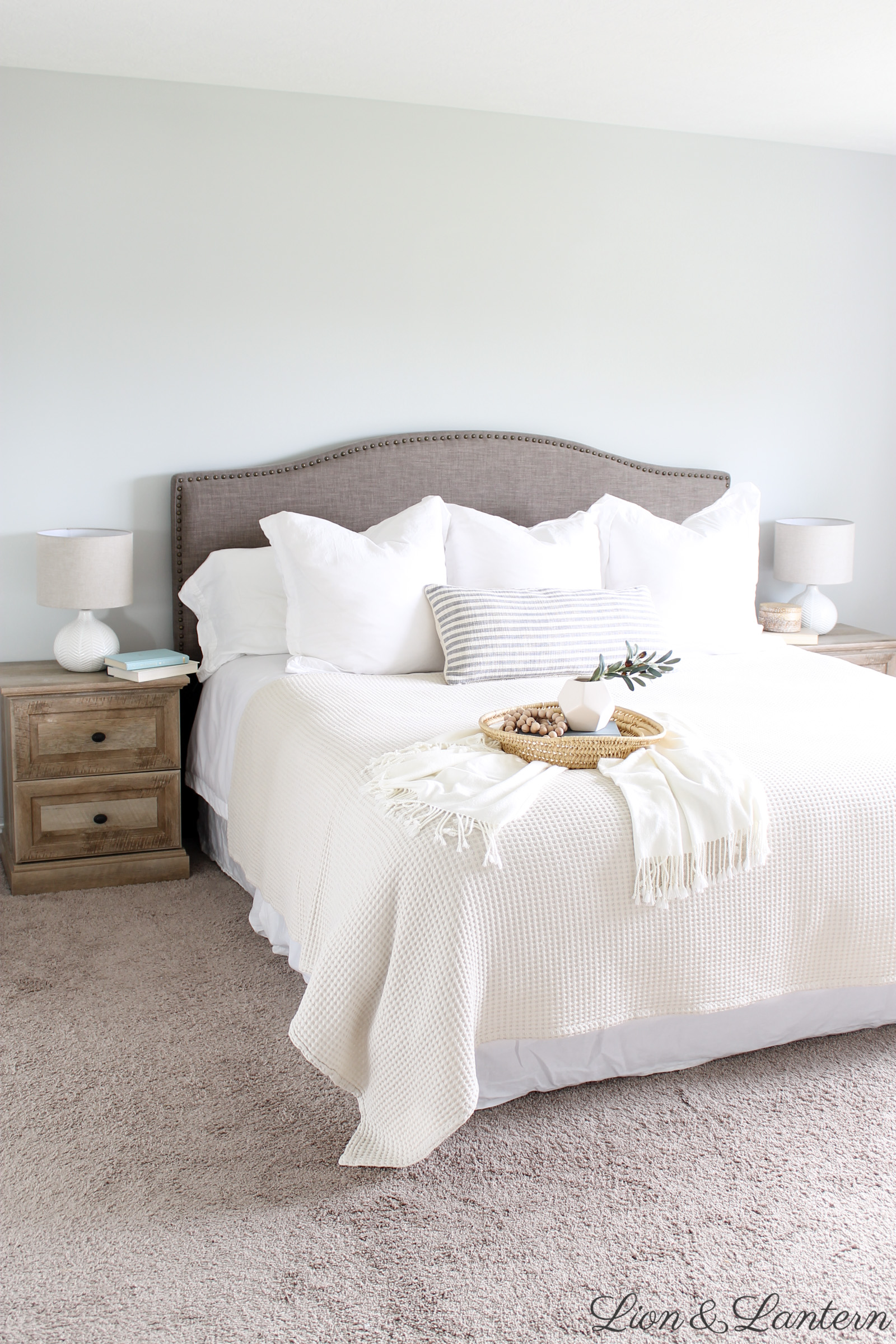 Modern Coastal Master Bedroom at LionAndLantern.com | coastal farmhouse, boho, minimalist, California, IKEA Hemnes dresser, white bedding, thrifted decor, upholstered headboard, baskets, books