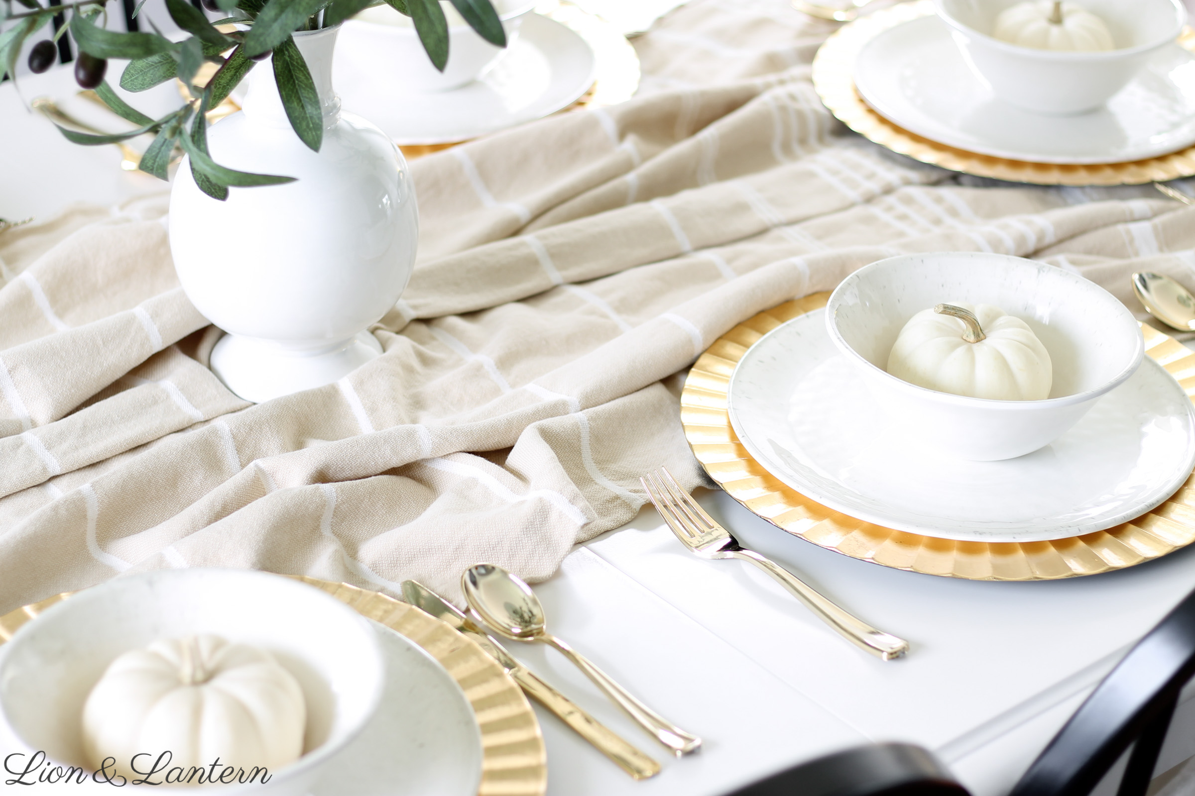 Simple Thanksgiving Tablescape at LionAndLantern.com | neutral thanksgiving, fall table decor, budget thanksgiving, farmhouse thanksgiving, white pumpkins, gold plate chargers, olive branches, rustic, traditional, white dishes